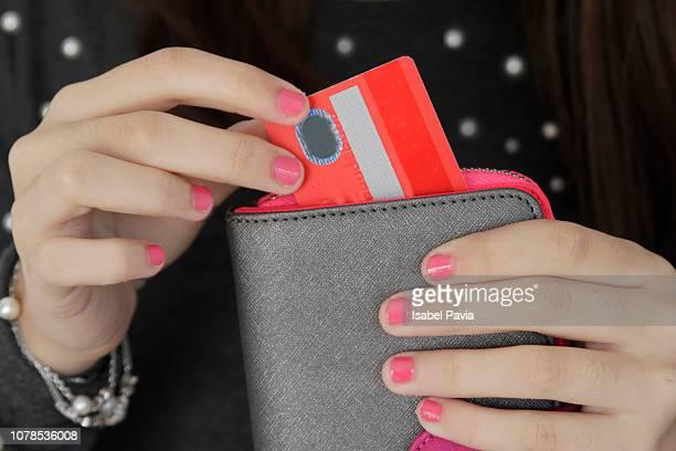 woman pulling credit card out of purse - sac à main rouge photos et images de collection