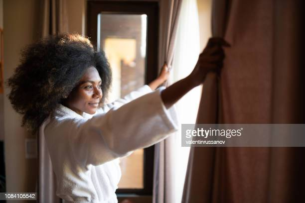 woman pulling curtains in hotel room - luxury hotel stock pictures, royalty-free photos & images