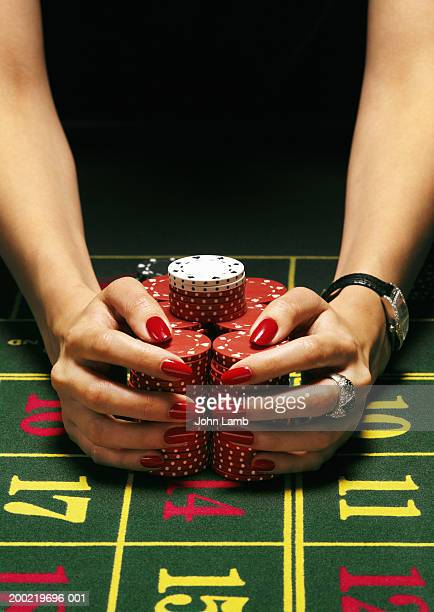Woman pulling gambling chips towards her in both hands, close-up