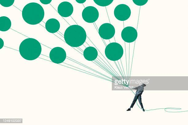 woman pulling green helium balloons with ropes - solutions stock pictures, royalty-free photos & images