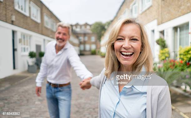 woman pulling her couple on the street - mature couple stock pictures, royalty-free photos & images