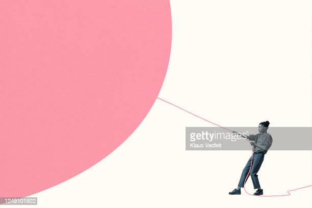 woman pulling large pink helium balloon with rope - strength stock pictures, royalty-free photos & images