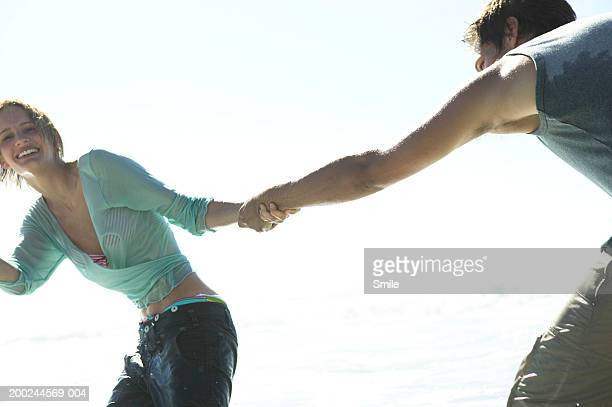 woman pulling man in water on beach - wet jeans stock photos and pictures