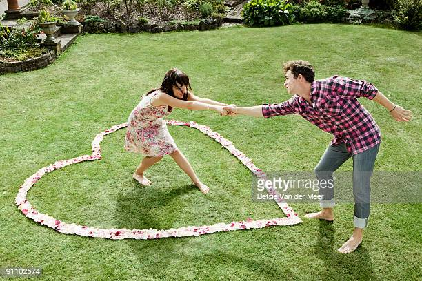 Woman pulling man into heartshaped rosepedals.