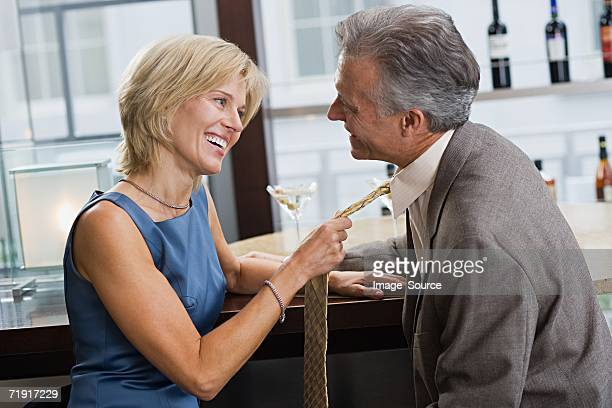 woman pulling man's tie - neckwear stock pictures, royalty-free photos & images