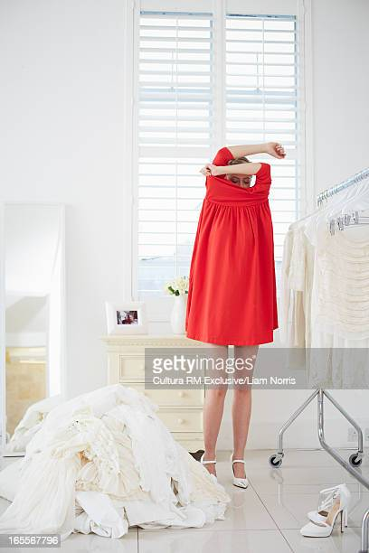 Woman pulling off red dress in bedroom