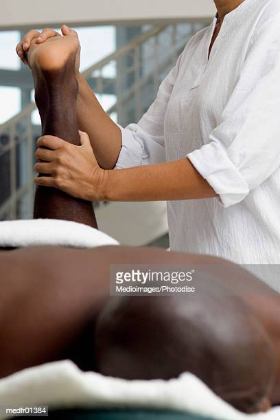 woman pulling on man's arm during massage treatment, close-up, part of - massage black woman stock photos and pictures