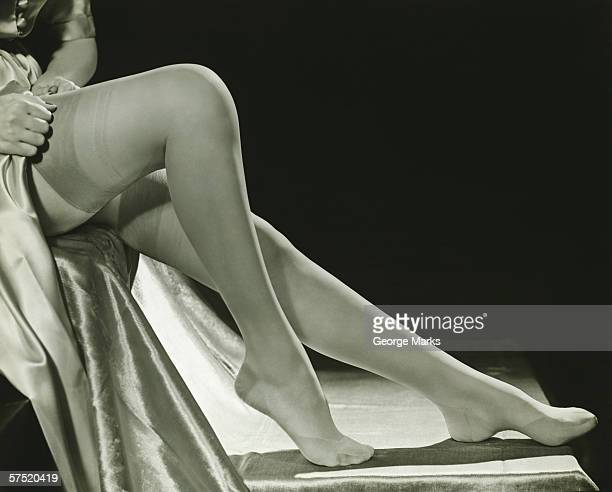 woman pulling on stockings, (b&w), low section - vintage stockings stock photos and pictures