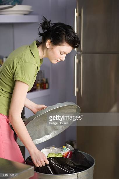 Woman pulling out rubbish bag from bin