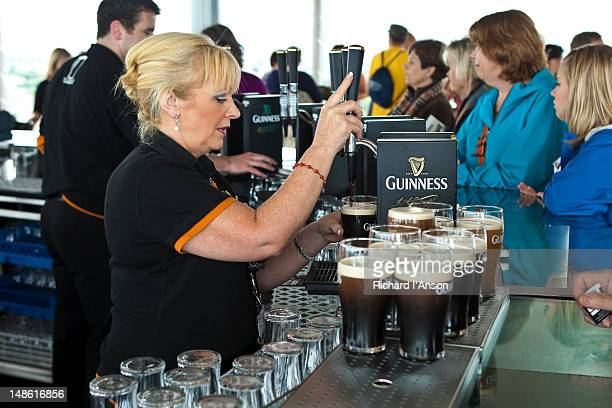 woman pulling pints of guinness at gravity bar at guinness storehouse. - guinness stock pictures, royalty-free photos & images