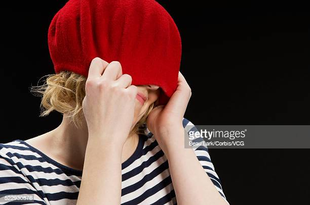 Woman pulling red hat down over her face
