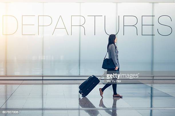 Woman pulling suitcase in airport departures hall