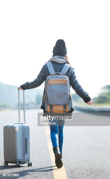 woman pulling suitcase walking on mountain highway - warm clothing stock pictures, royalty-free photos & images