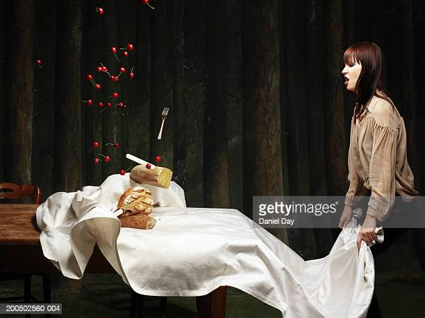 Woman pulling tablecloth off table