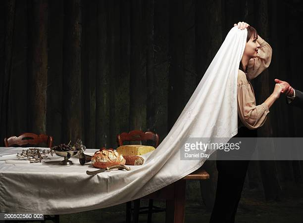 Woman pulling tablecloth over her head