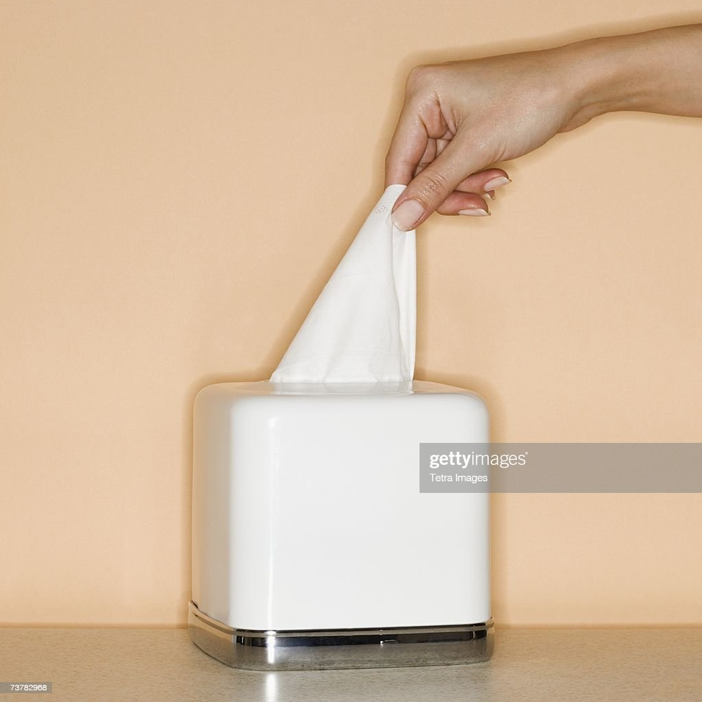 Woman pulling tissue out of box : Foto de stock