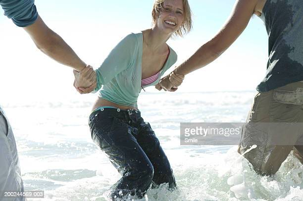 woman pulling two men in water on beach - wet jeans stock photos and pictures