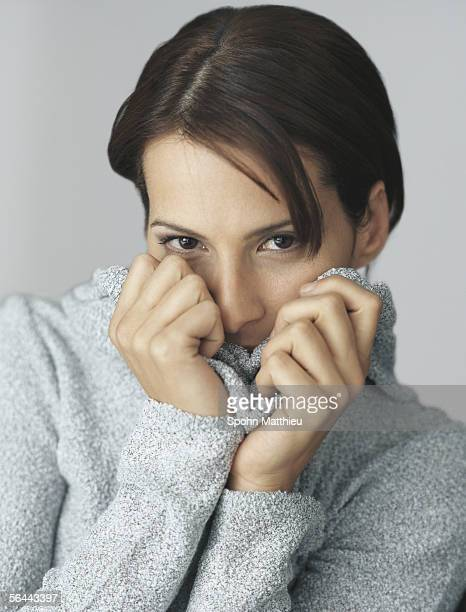 Woman pulling up sweater over mouth, portrait