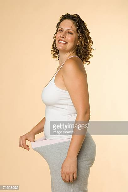 woman pulling waistband - waistband stock pictures, royalty-free photos & images