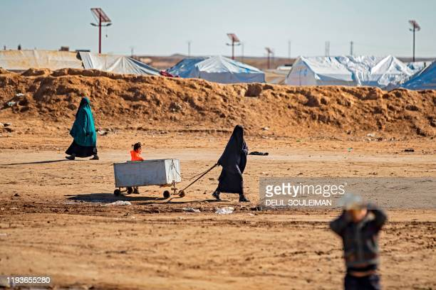 Woman pulls a cart with a child trailing her at the Kurdish-run al-Hol camp for the displaced in the al-Hasakeh governorate in northeastern Syria on...