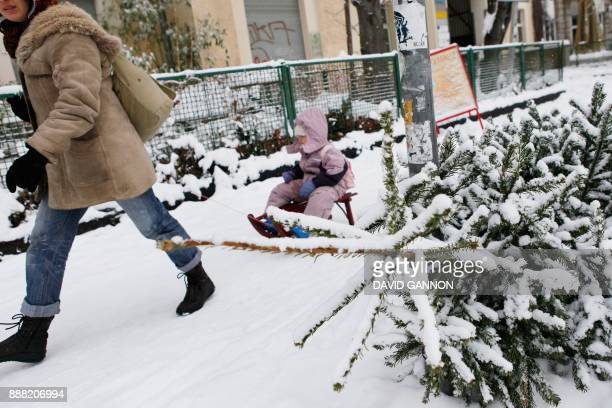 A woman pulls a child on a sledge past a discarded Christmas tree covered with snow in Berlin's Kreuzberg district January 2 2010 Winter weather...