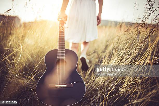 woman pulls a guitar through a field
