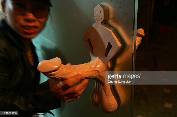 A woman pulls a handle of a toilet at the theme park 'Love Land' on October 24 2009 in Jeju South Korea Love Land is an outdoor sexthemed sculpture...
