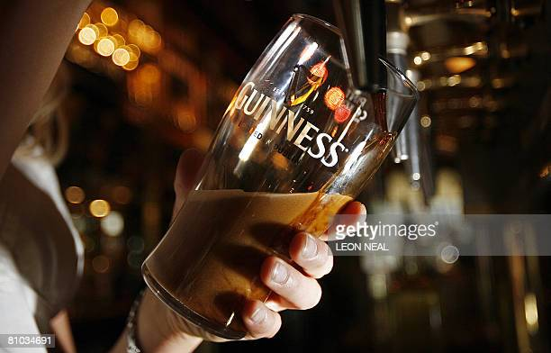 A woman pulls a pint of Guinness beer in London on May 9 2008 Diageo the alcoholic beverages giant said Friday it plans to overhaul its Guinness...