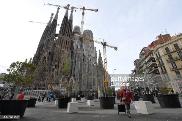 A woman pulls a shopping trolley close to the Sagrada Famila Basilica in Barcelona on January 3 2018 The Sagrada Familia basilica which was among the...