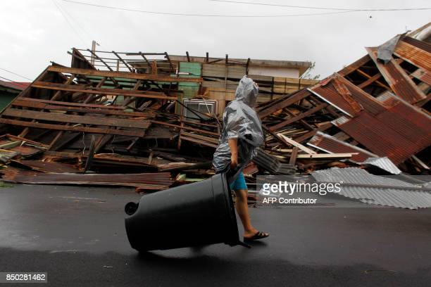 A woman pulls a trash can past a destroyed home as Hurricane Maria hits Puerto Rico in Fajardo on September 20 2017 Maria made landfall on Puerto...