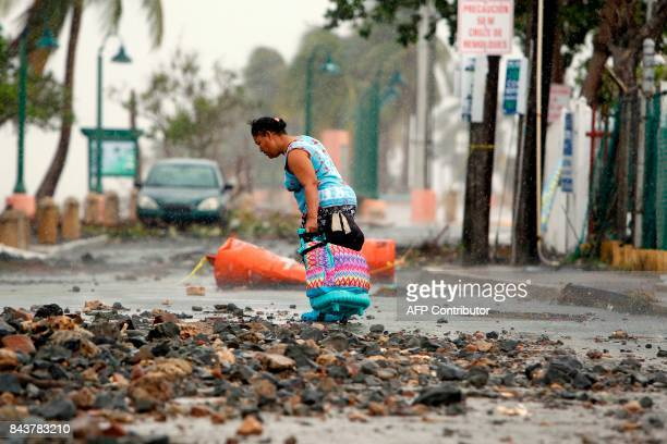 TOPSHOT A woman pulls a travel case on a rock scattered road in the aftermath of Hurricane Irma in Fajardo Puerto Rico on September 7 2017 One of the...