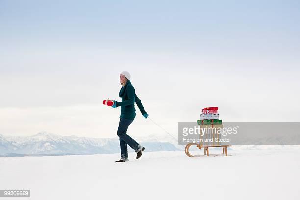 Woman pulls Christmas presents on sled