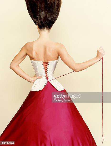 Woman pulls corset tight around waist