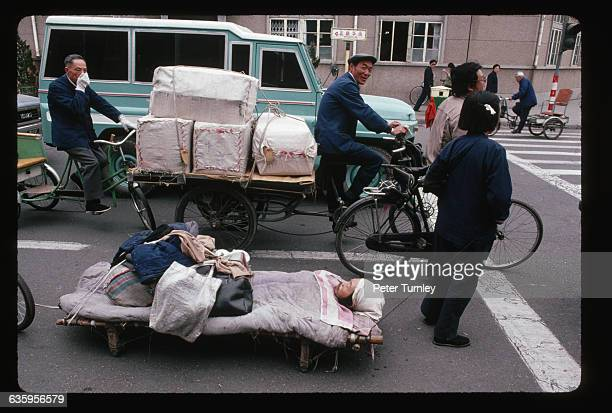 A woman pulls her husband on a makeshift rolling stretcher through the streets of Beijing