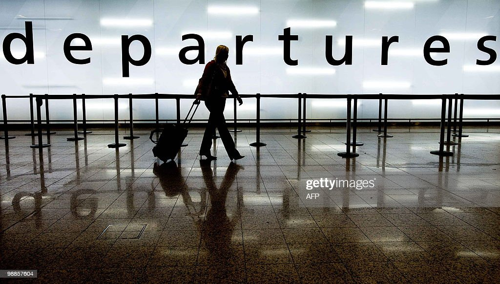 A woman pulls her suitcase as she walks : News Photo