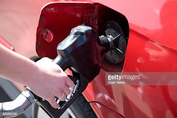 Woman pumping gas.