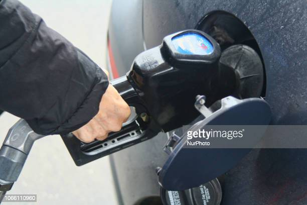 Woman pumping gasoline into her car at a gasoline station in Maple Ontario Canada