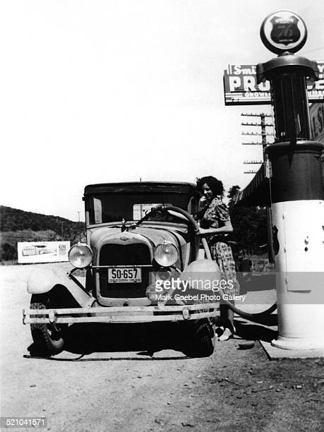 Woman pumping gasoline into vintage automobile late 1930s