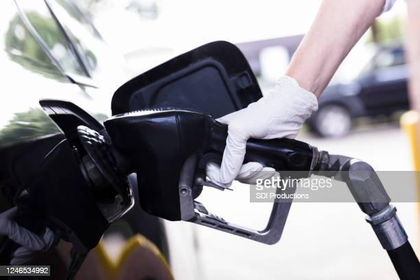 woman pumps gas during coronavirus pandemic - abastecer imagens e fotografias de stock