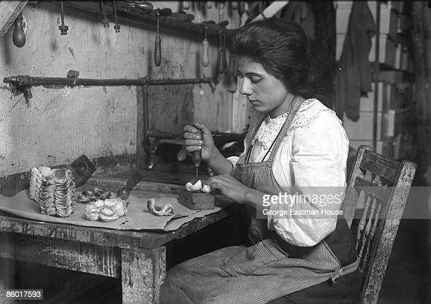 A woman punches a hole in the material while making artificial roses in a tenement factory in New York city possibly in the Lower East Side 1911