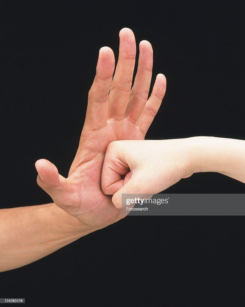 Woman punching palm of man : Stock Photo