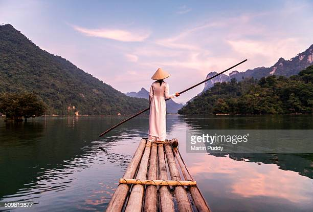 woman punting bamboo raft across lake - vietnam stock pictures, royalty-free photos & images