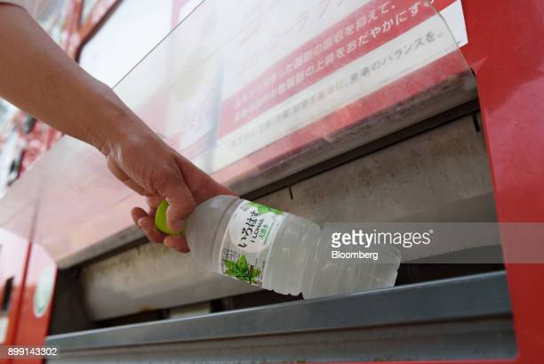 A woman purchases a bottle of water from a vending machine in Kawasaki City Kanagawa Prefecture Japan on Friday June 23 2017 Japan's November retail...