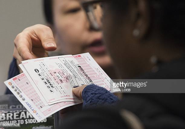 A woman purchases a Powerball lottery ticket at a convenience store in Washington DC January 7 2016 Lottery officials predict Saturday's jackpot will...