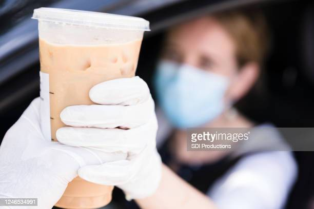 woman purchases iced coffee at coffee shop drive through - covering stock pictures, royalty-free photos & images