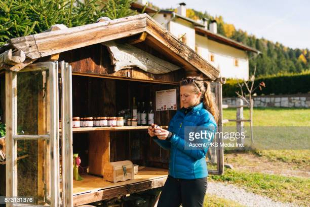 woman purchases local products at small alpine trail - jam media fotografías e imágenes de stock