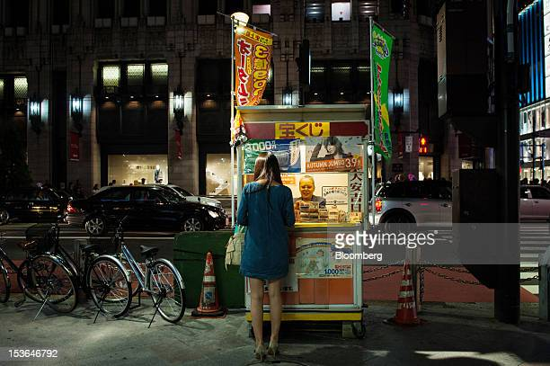 A woman purchases lottery tickets at a kiosk at night in Tokyo Japan on Sunday Oct 7 2012 The world's finance ministers and central bank governors...
