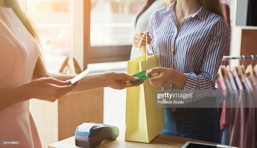 Woman purchasing clothes with credit card : Stock Photo