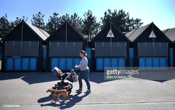 Woman pushes a baby buggy as she walks a dog past closed-down stalls at an empty Harbour Market in Whitstable, south east England on April 11 as life...