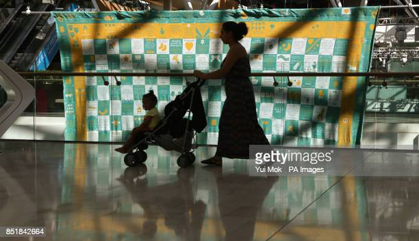 A woman pushes a baby buggy past a giant baby blanket during the unveiling of Pampers' attempt to knit a recordbreaking baby blanket made up of...